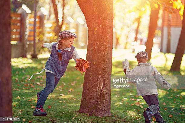Brother and sister playing tag in autumn park