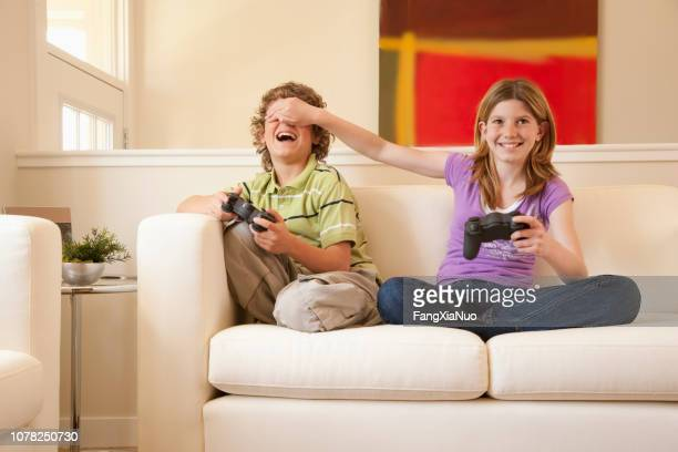 brother and sister playing video games at home together - teasing stock pictures, royalty-free photos & images