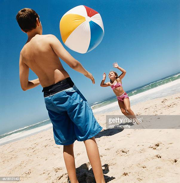 brother and sister playing with a beach ball on a beach - knaben in badehosen stock-fotos und bilder