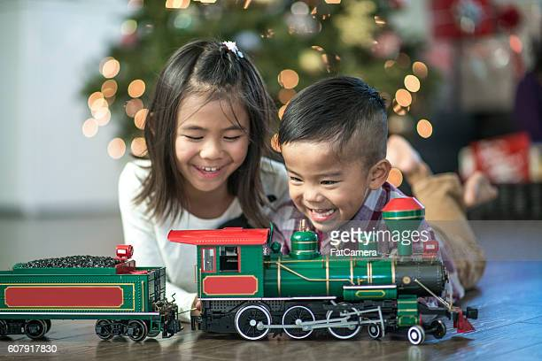 Brother and Sister Playing with a Train