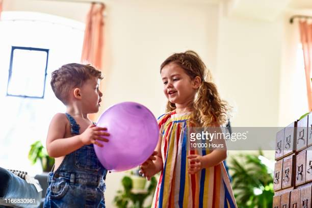 brother and sister playing with balloon - boys stock pictures, royalty-free photos & images