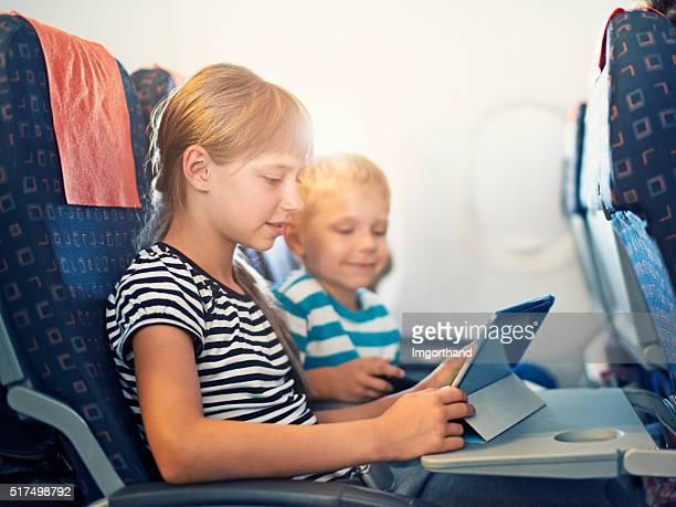 Bruder und Schwester spielen mit Tablet im Flugzeug