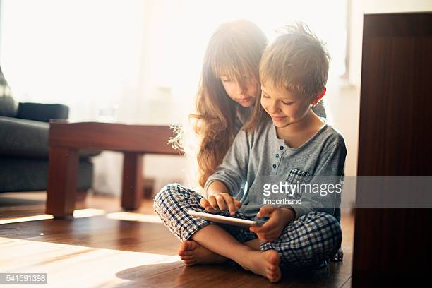 Brother and sister playing with tablet on the floor