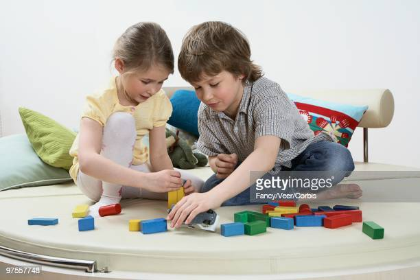 brother and sister playing with toy blocks - boys wearing tights stock photos and pictures