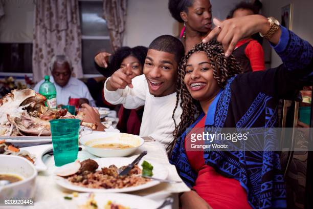 brother and sister posing at dinner table - black family dinner stock photos and pictures