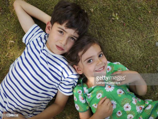 2 brother and sister posing together in the garden - seulement des enfants photos et images de collection