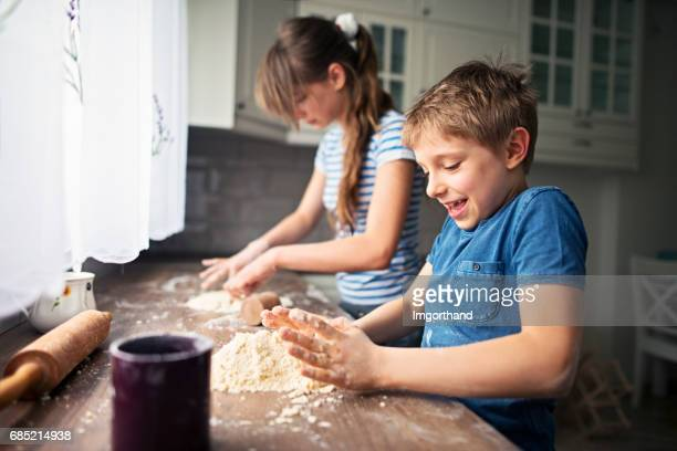 Brother and sister preparing dough for baking cookies