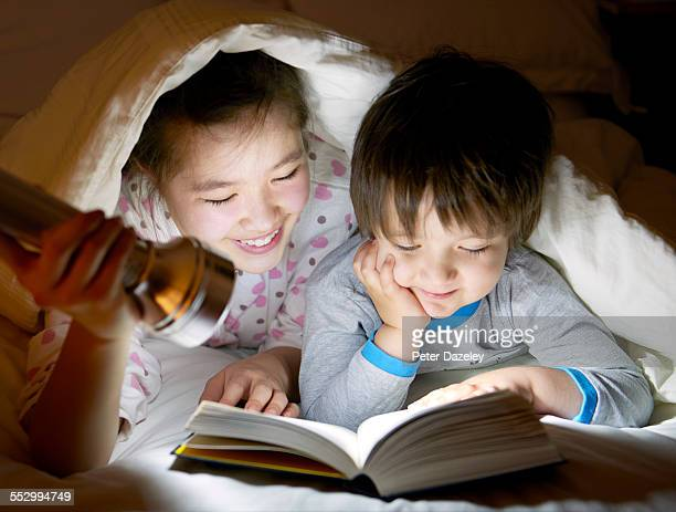 Brother and sister reading under the covers