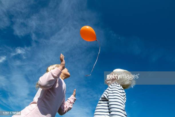 brother and sister releasing a balloon - releasing stock pictures, royalty-free photos & images