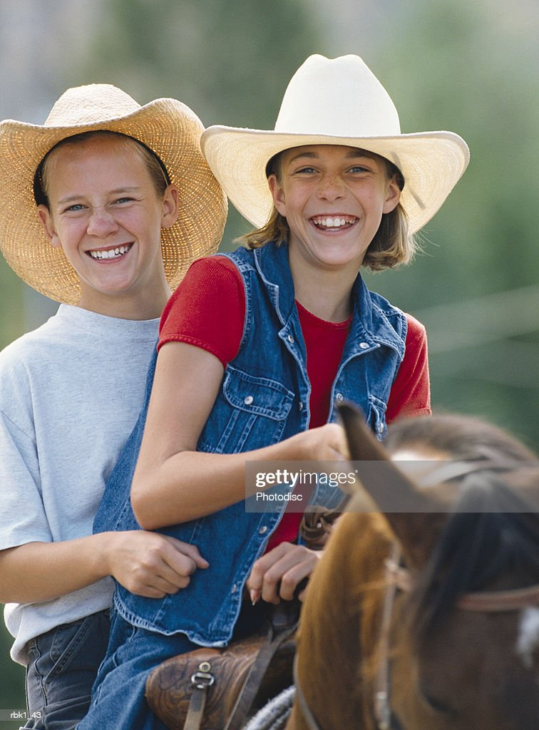 Brother and sister (12-14) riding horse, smiling : Stockfoto