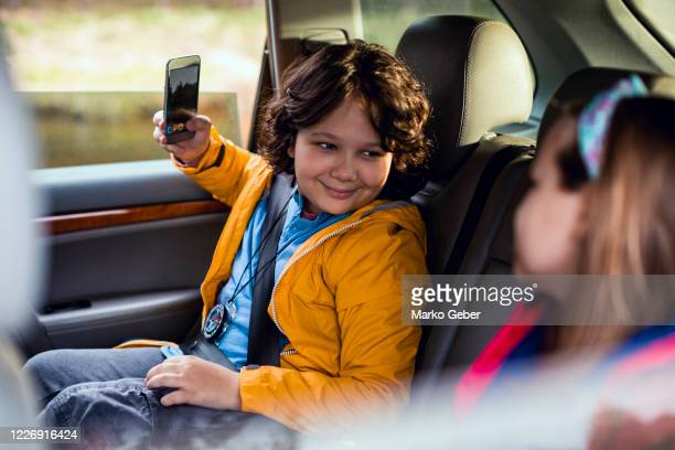 brother and sister riding in the back seat - outdoor pursuit stock pictures, royalty-free photos & images