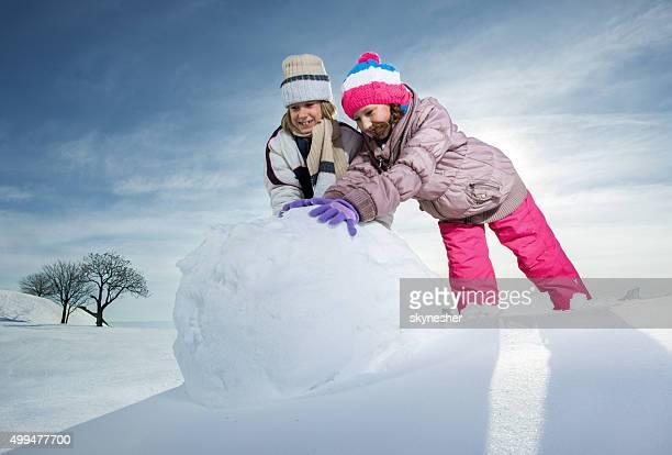 Bruder und Schwester rolling Schneeball machen Schneemann.