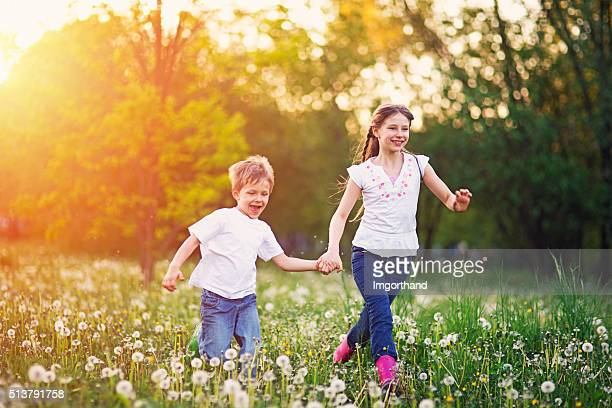 Brother and sister running in dandelion field.