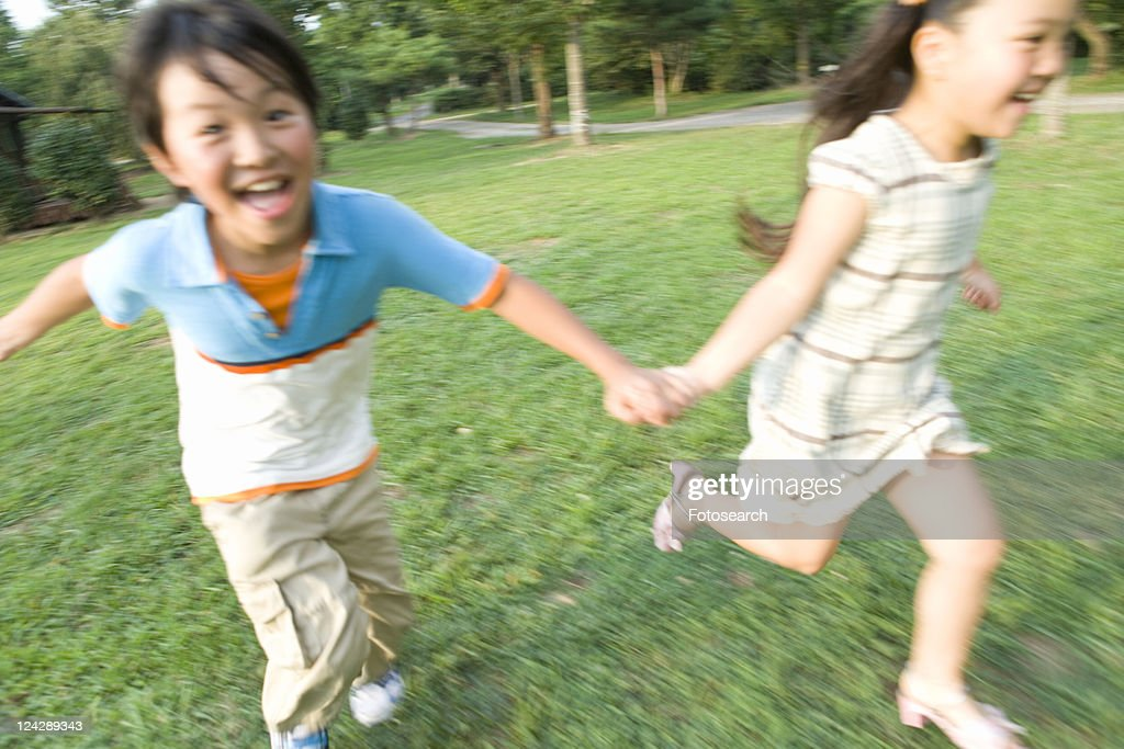 Brother and Sister Running in Field : ストックフォト