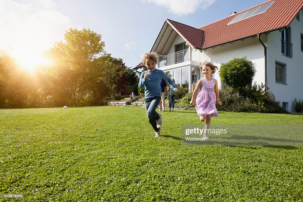 Brother and sister running in garden : Stock Photo