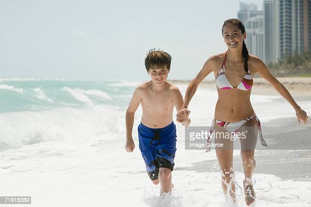 Brother and sister running in the sea