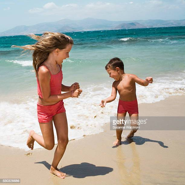A brother and sister running on a beach.