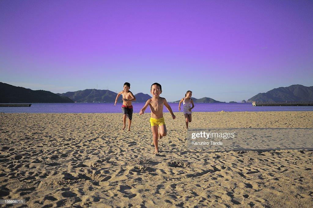 Brother and sister running on the beach : Bildbanksbilder
