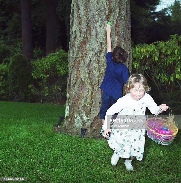Brother and sister (4-6) searching for Easter eggs