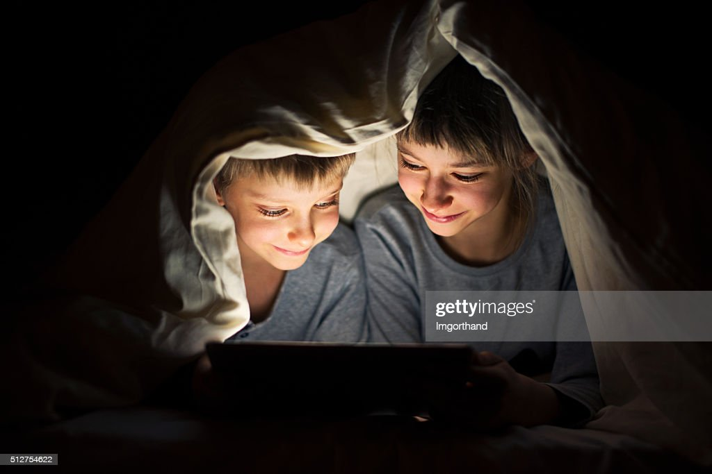 Brother and sister secretly reading book on digital tablet : Stock Photo
