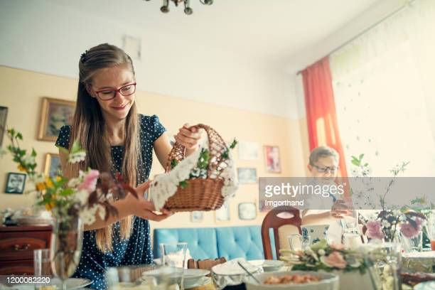 brother and sister setting the table for traditional easter breakfast - easter basket stock pictures, royalty-free photos & images