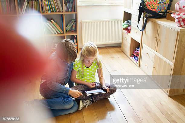 Brother and sister sharing and using digital tablet