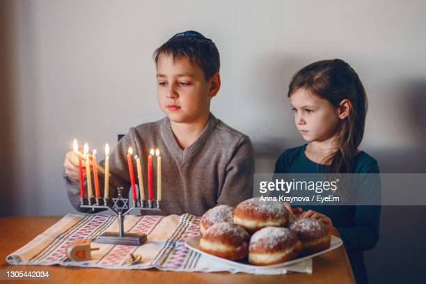 brother and sister siblings lighting candles on menorah for jewish hanukkah holiday at home. - sufganiyah stock pictures, royalty-free photos & images
