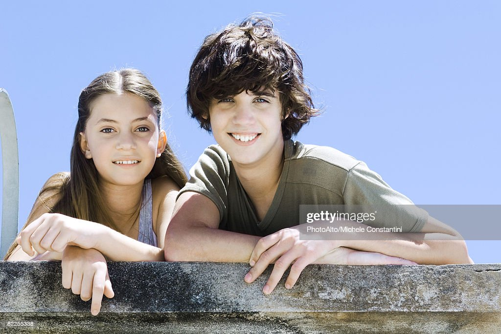 Brother and sister side by side, leaning on concrete wall, smiling at camera, portrait : Stock Photo