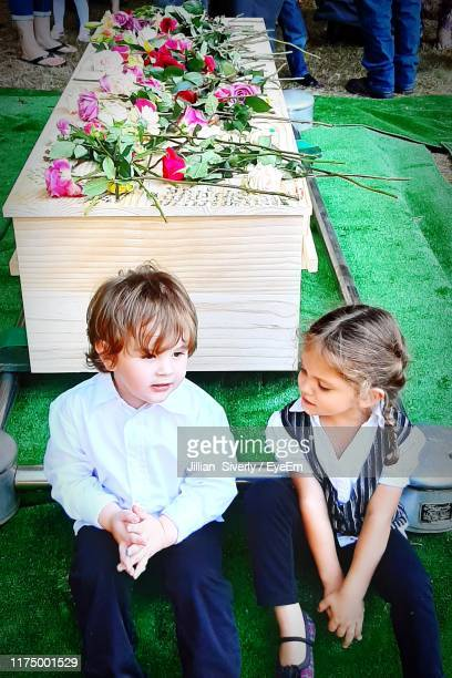 brother and sister sitting against coffin with flowers - sarg stock-fotos und bilder