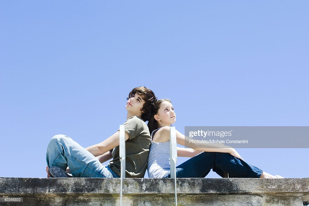 Brother and sister sitting back to back, looking up and away : Stock Photo