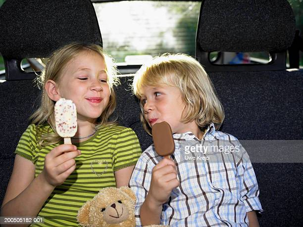 Brother and sister (4-7) sitting in car, eating ice cream, smiling