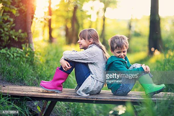 Brother and sister sitting on bridge in forest