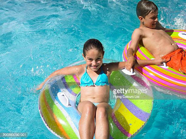 Brother and sister (9-12) sitting on inflatables in swimming pool