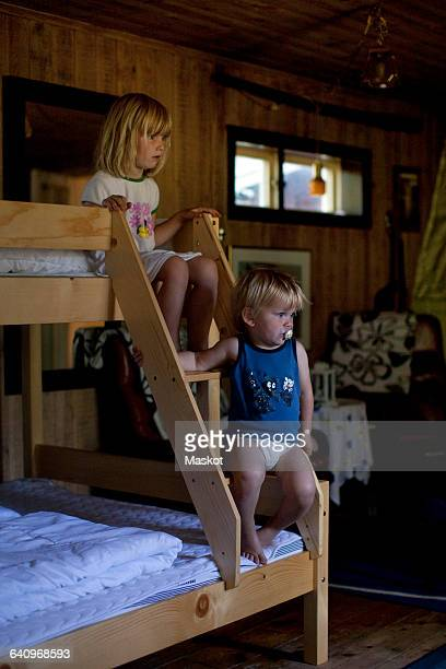 Brother and sister sitting on steps of bunkbed at home