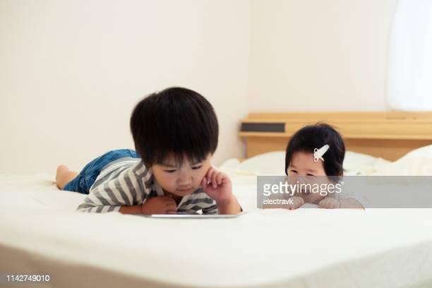 一緒にベッドに座っている兄と妹 - 4歳から5歳 ストックフォトと画像
