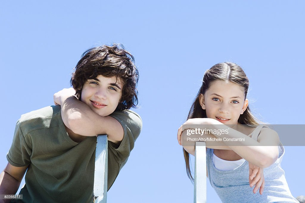 Brother and sister sitting sideways in chairs, leaning on elbows, smiling at camera : Stock Photo