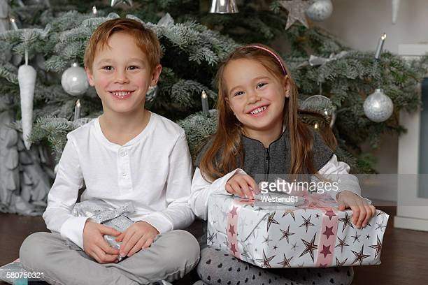 Brother and sister sitting with Christmas presents in front of Christmas tree