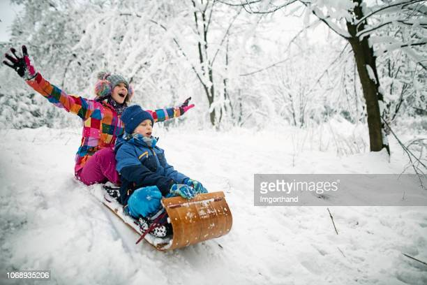 Brother and sister  sledding in winter.