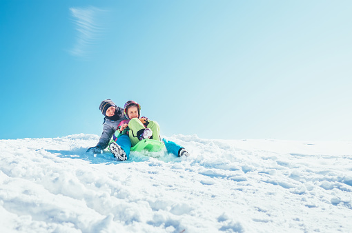 Brother and sister slide down from the snow slope sitting in one slide. Enjoying the winter sledding time 1041872426