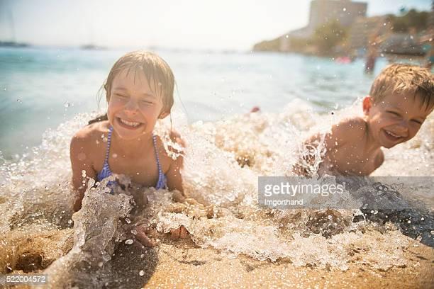 Bruder und Schwester spashed von Wellen