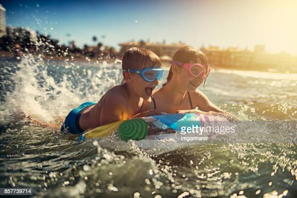 brother and sister splashing in summer sea - very young tube stock photos and pictures
