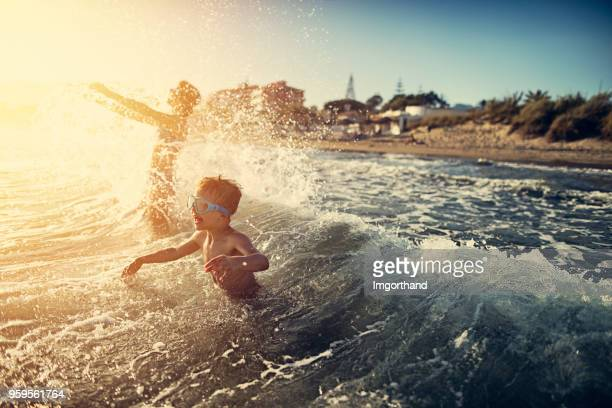 brother and sister splashing in summer sea - carefree stock pictures, royalty-free photos & images