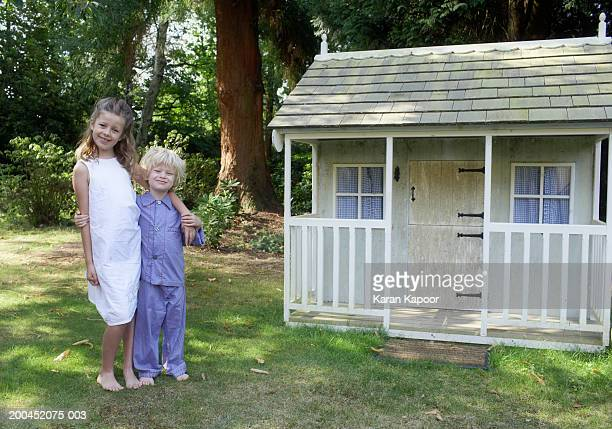 Brother and sister (4-9) standing by playhouse in garden, smiling