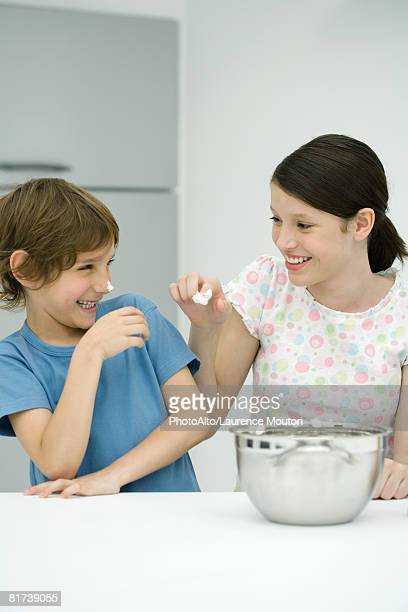 Brother and sister standing in kitchen, girl putting whipped cream on boy's nose, both smiling