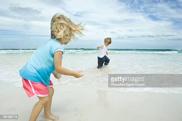 brother and sister standing in surf - unrecognisable person stock pictures, royalty-free photos & images