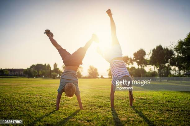 brother and sister standing on hands on grass - handstand stock pictures, royalty-free photos & images