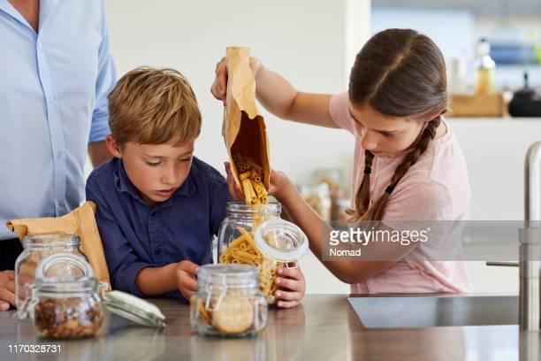 brother and sister storing pasta in jar at kitchen - saco objeto manufaturado imagens e fotografias de stock
