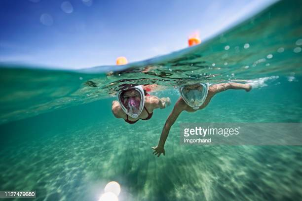 brother and sister swimming underwater in sea - snorkeling stock pictures, royalty-free photos & images