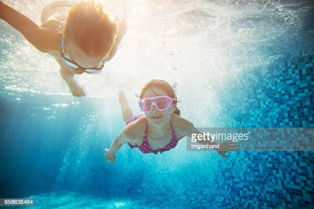 Brother and sister swimming underwater
