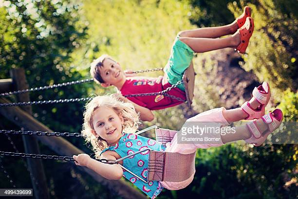 Brother and sister swinging and having fun